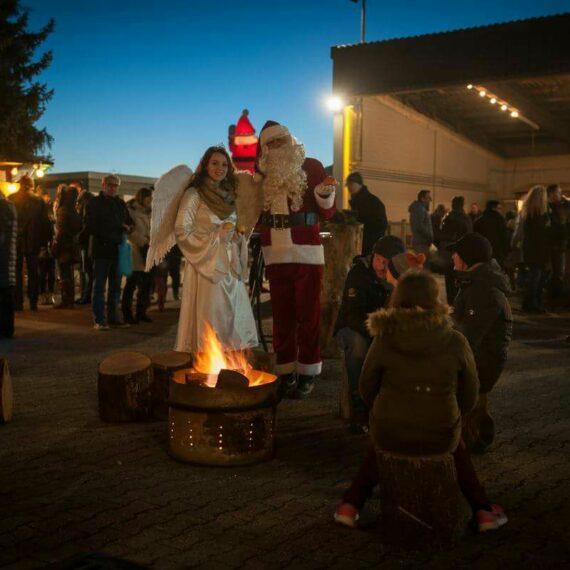 Schumacher Weihnachtsmarkt mit einem Engel und dem Weihnachtsmann die vor einer großen Feuerschale stehen