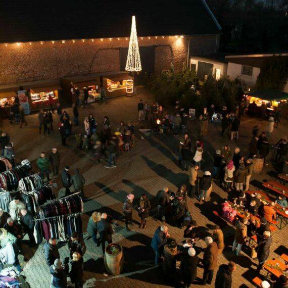 Schumacher Weihnachtsmarkt von oben, mit schöner Weihnachtsbeleuchtung und Tischen und Bänken zum Sitzen sowie Verkaufsstände im Innenhof
